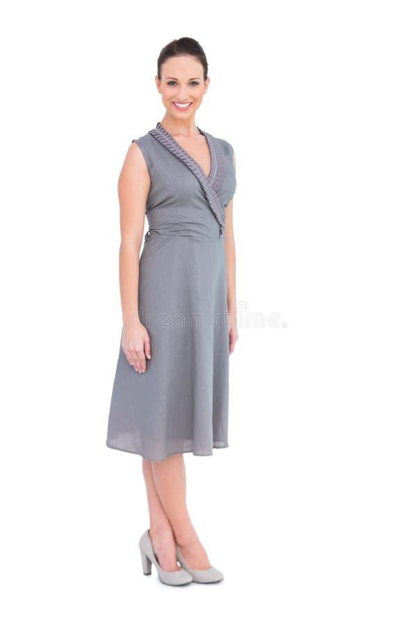 Donna elegante felice nella posa di classe del vestito fotografia stock