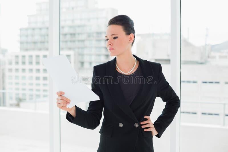 Donna elegante seria che legge un documento in ufficio fotografie stock