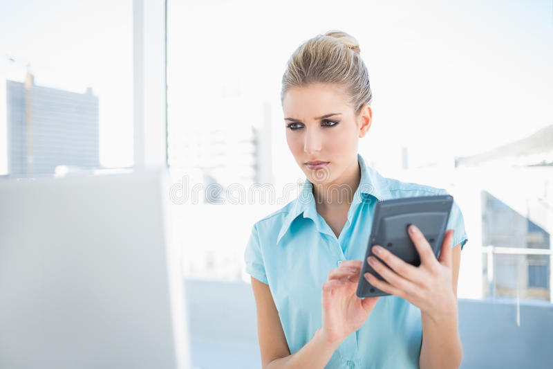 Donna elegante seria che per mezzo del calcolatore che esamina computer portatile fotografia stock