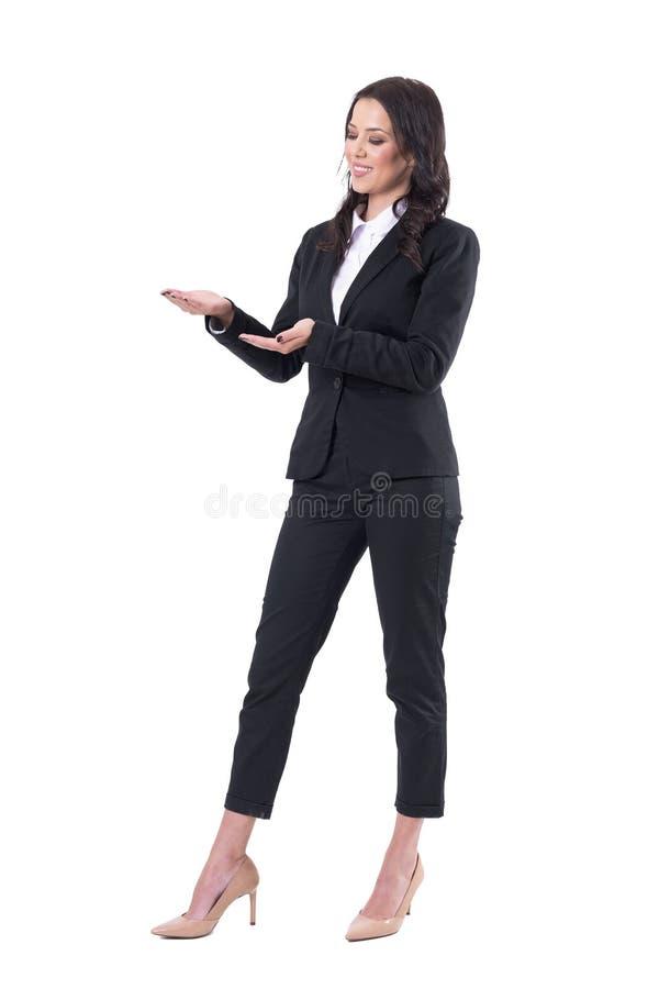 Donna elegante sorridente di affari in vestito convenzionale nero che presenta copyspace con le palme aperte fotografia stock