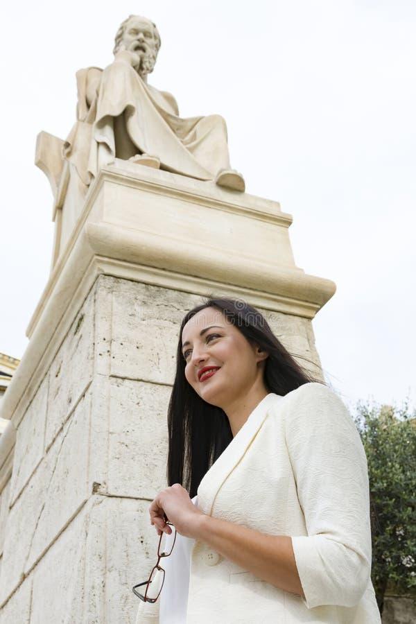 Donna elegante sotto la statua di Socrates fotografia stock