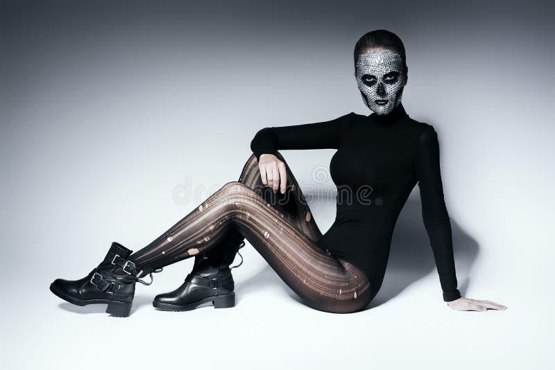 Donna elegante spaventosa che posa sul pavimento fotografie stock libere da diritti