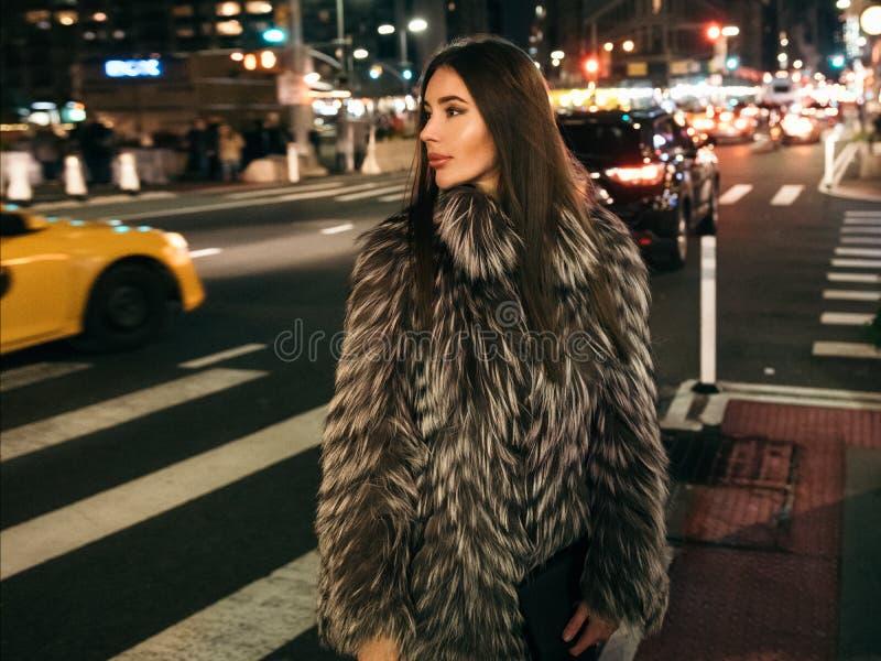 Donna elegante splendida che cammina sulla via della città di notte che porta il rivestimento falso della pelliccia e che tiene b immagini stock libere da diritti
