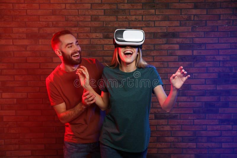 Donna emozionale che gioca i video giochi con la cuffia avricolare di VR e l'uomo felice vicino a bric fotografia stock