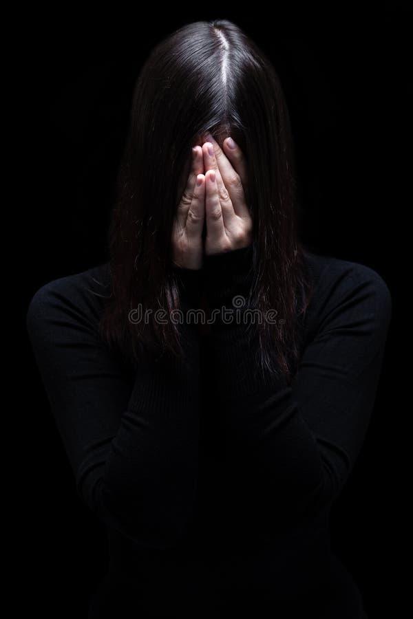 Donna emozionale che grida e che copre il fronte di mani che nascondono gli strappi fotografia stock