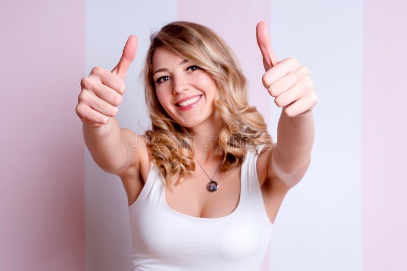 Donna emozionale felice che posa e che mostra i pollici su su fondo rosa Giovane donna bionda che d? i pollici su, approvando fotografia stock
