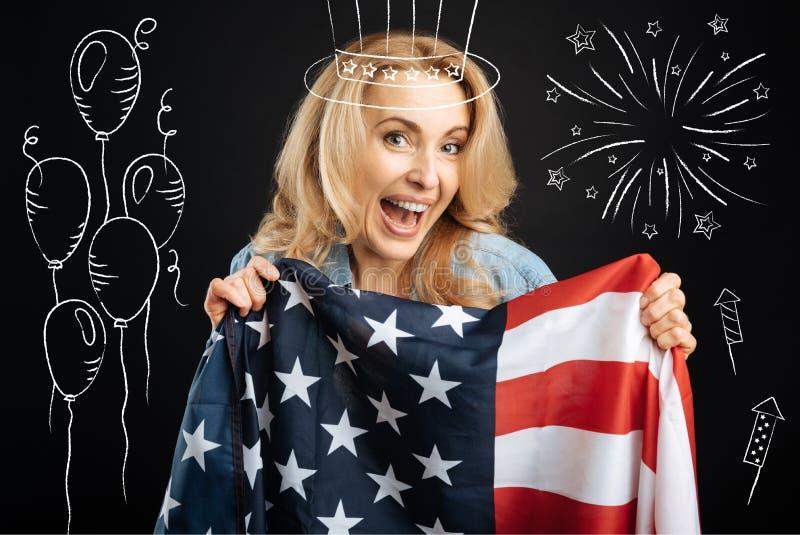 Donna emozionale felice che tiene la bandiera americana immagine stock