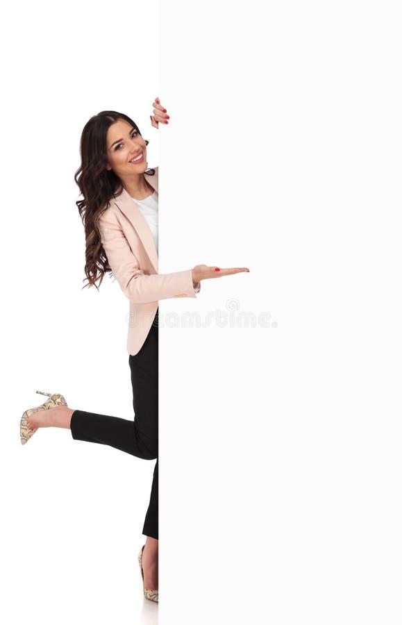 Donna emozionante che presenta grande bordo in bianco con un vantaggio fotografie stock libere da diritti