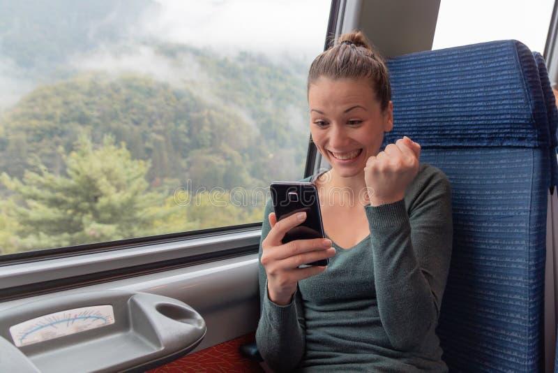 Donna emozionante che tiene uno smartphone e che vince sulla linea sul viaggio in treno fotografie stock