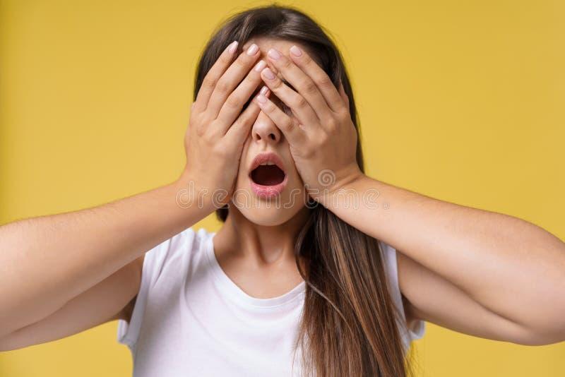 Donna emozionante sorpresa felice che copre di mani il suo occhio con lo spazio in bianco della copia, bella donna del ritratto E immagine stock libera da diritti