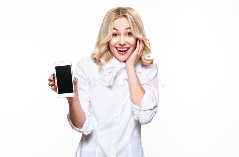 Donna emozionante splendida che mostra il telefono cellulare dello schermo in bianco sopra fondo bianco, celebrando vittoria e su fotografie stock