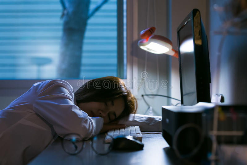 Donna esaurita sonnolenta che lavora alla scrivania con il suo computer portatile O immagini stock libere da diritti