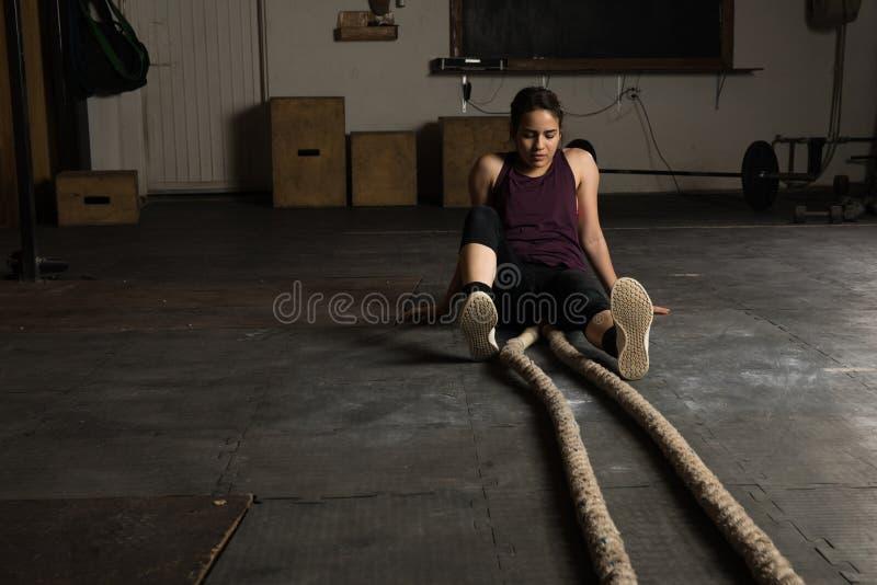 Donna esaurita in una palestra di inter-addestramento fotografia stock