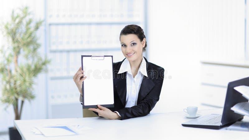 Donna esecutiva di affari che mostra foglio bianco, sedentesi al suo scrittorio fotografia stock