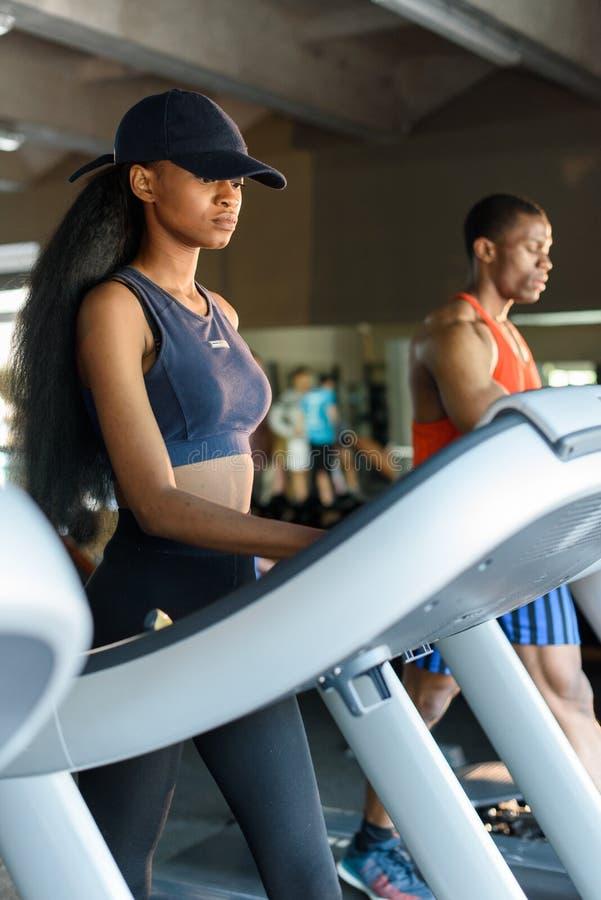 Donna esile afroamericana sexy con il suo istruttore atletico bello nero sulla pedana mobile in palestra Concetto di forma fisica immagine stock