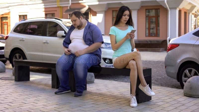 Donna esile che trascura uomo di peso eccessivo, rifiuto sociale, pregiudizi di obesità, salute immagine stock
