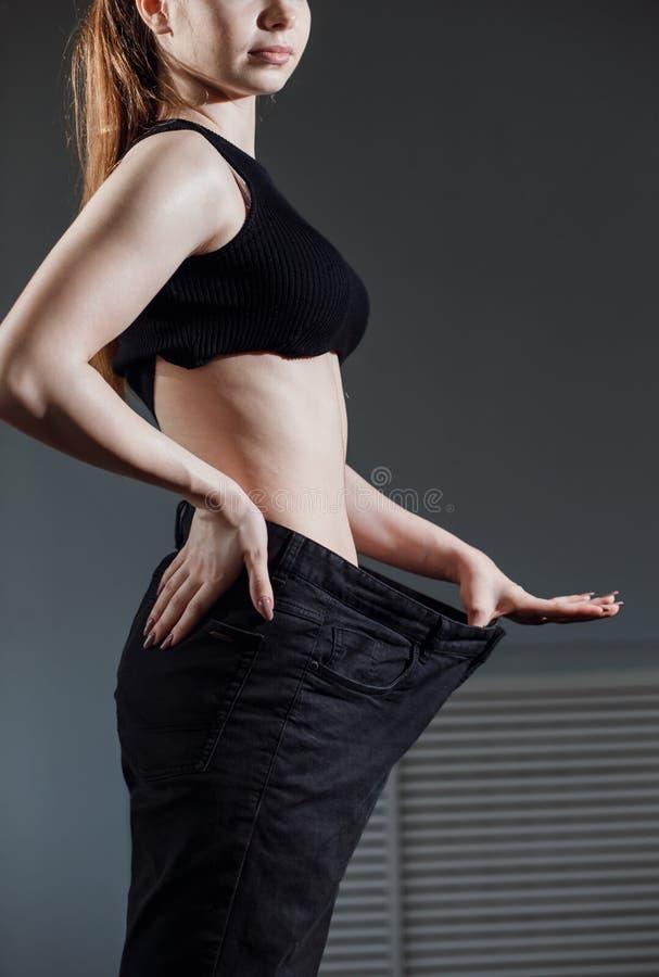 Donna esile con l'ente sottile sano, mostrantele i vecchi jeans dopo la riuscita dieta fotografia stock