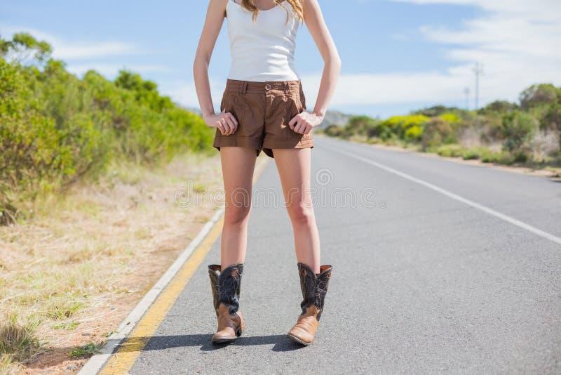 Donna esile naturale che posa mentre facendo auto-stop fotografie stock