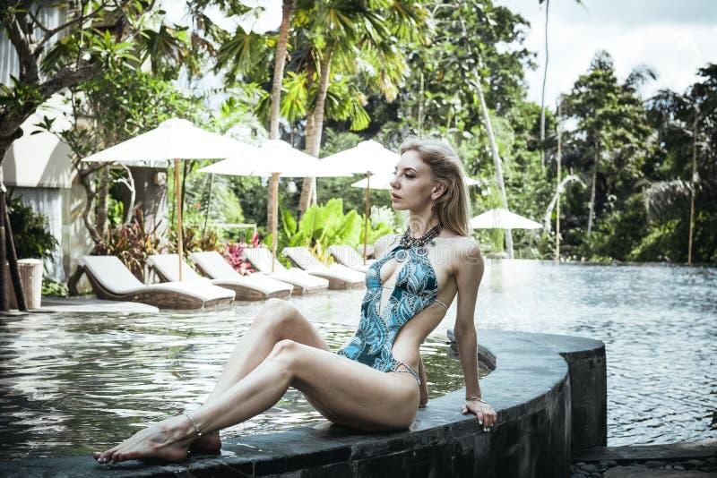 Donna esile sexy alla piscina della villa tropicale, isola di Bali, Indonesia immagini stock