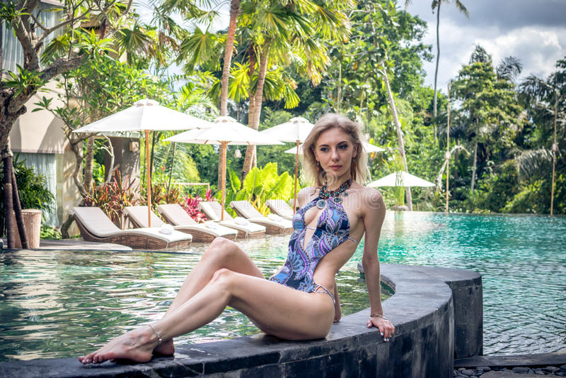 Donna esile sexy alla piscina della villa tropicale, isola di Bali, Indonesia fotografie stock libere da diritti