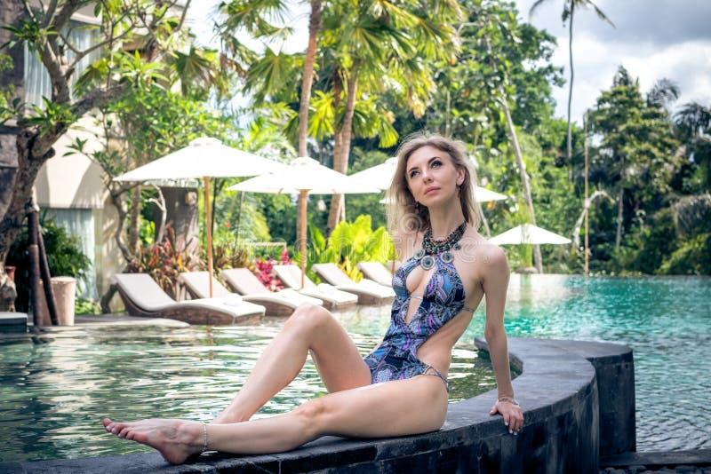 Donna esile sexy alla piscina della villa tropicale, isola di Bali, Indonesia fotografie stock