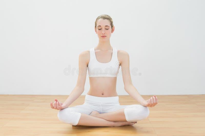 Donna esile sveglia che medita seduta nella posizione di loto nella palestra fotografia stock libera da diritti