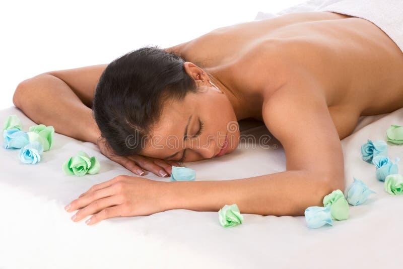 Donna etnica in stazione termale che si distende sulla tabella di massaggio fotografia stock