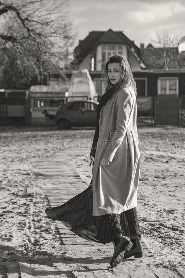 Donna europea splendida in cappotto e vestito caldi su una passeggiata in parco vicino al fiume Tempo ventoso I suoi vestiti vola immagini stock