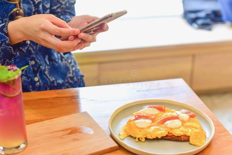 Donna facendo uso di Smartphone per prendere la foto dell'alimento immagine stock libera da diritti