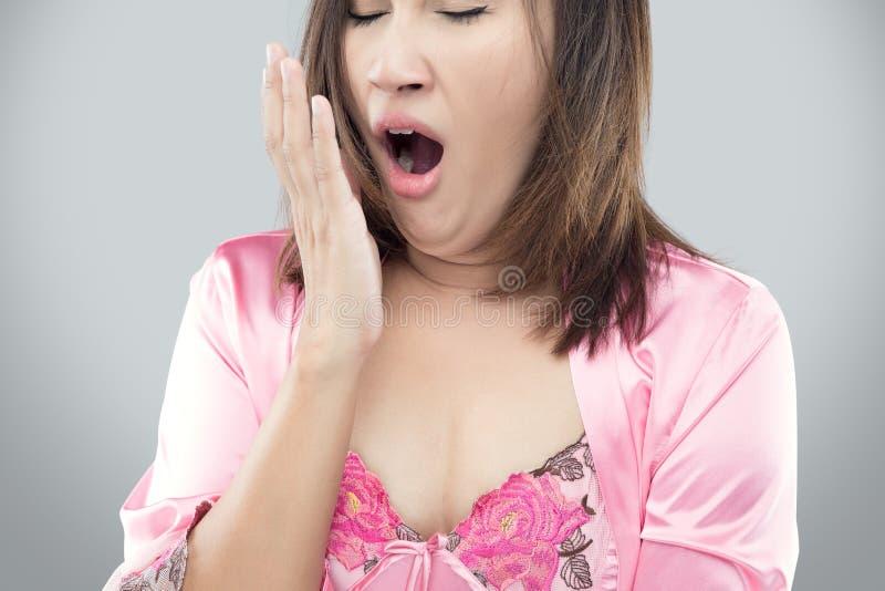 Donna faticosa di sbadiglio Bello modello asiatico isolato sulla parte posteriore di gray immagine stock