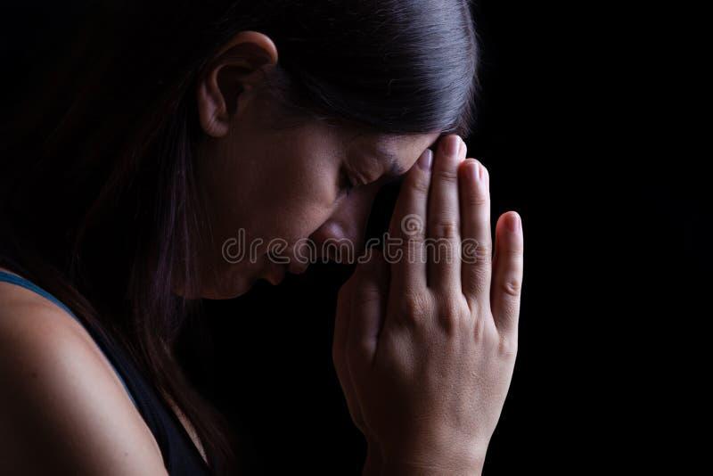 Donna fedele che prega, con le mani piegate nel culto che tocca la fronte fotografia stock libera da diritti