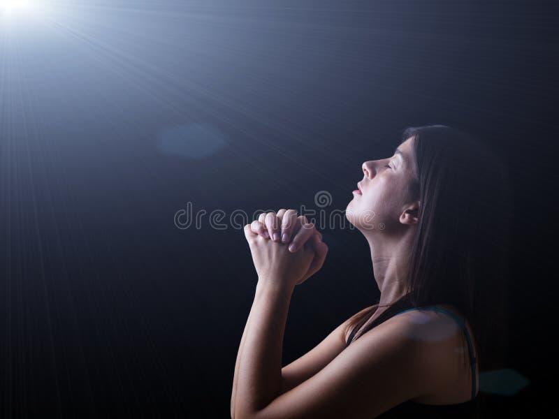 Donna fedele che prega nell'ambito di una luce divina o celeste fotografia stock libera da diritti