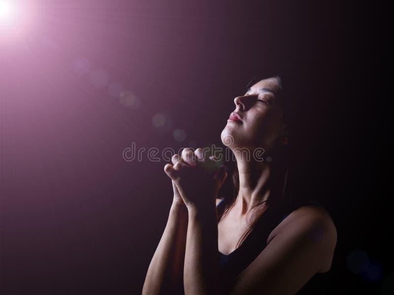 Donna fedele che prega nell'ambito di una luce divina o celeste fotografie stock