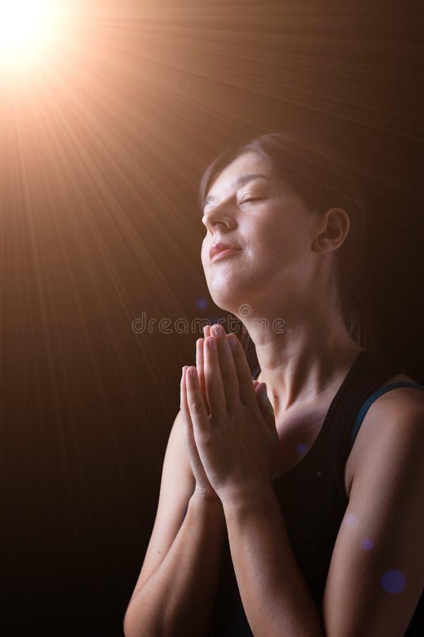 Donna fedele felice che prega e che sorride nella felicità immagine stock libera da diritti