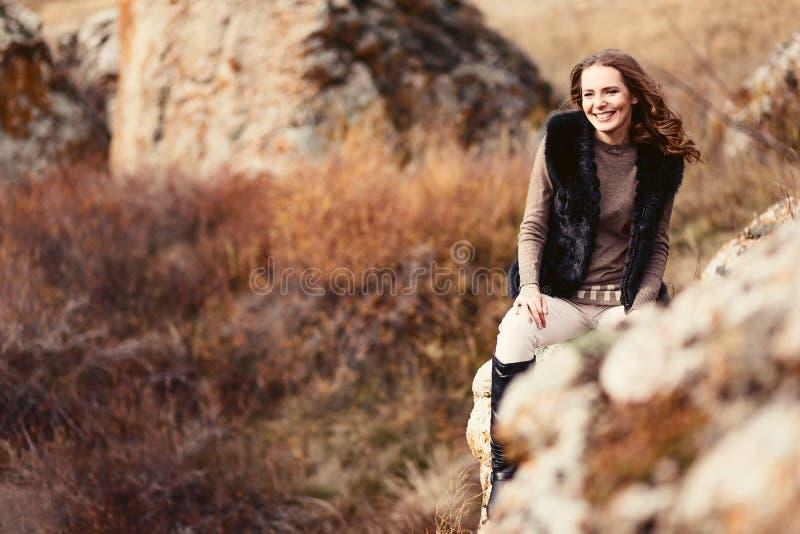Donna felice allegra che si siede nelle montagne in autunno, maglione caldo fotografie stock libere da diritti