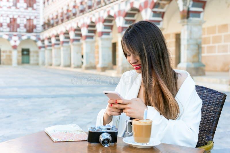Donna felice attraente che mangia un caffè su una via a fotografie stock libere da diritti