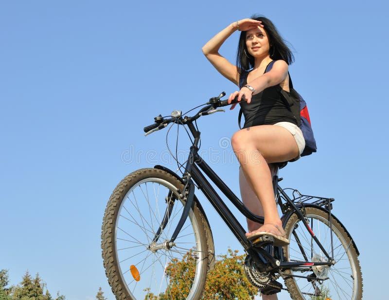 Donna felice attraente con la bici fotografia stock