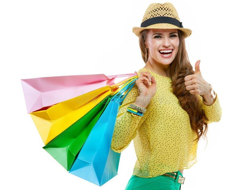 Donna felice in cappello con i sacchetti della spesa che mostrano i pollici su immagine stock