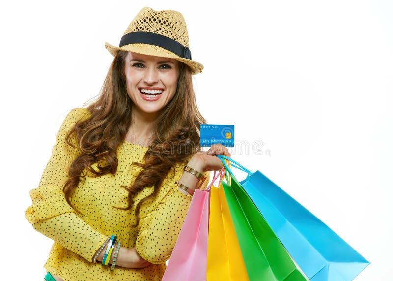 Donna felice in cappello con i sacchetti della spesa che mostrano la carta di credito immagini stock libere da diritti