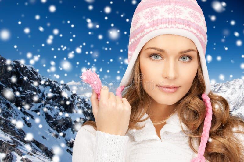 Donna felice in cappello di inverno sopra neve e le montagne fotografia stock