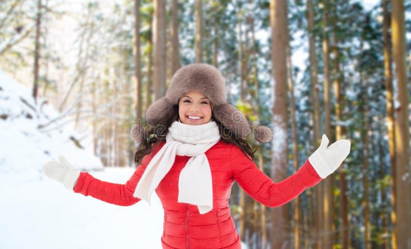 Donna felice in cappello di pelliccia sopra la foresta di inverno fotografia stock