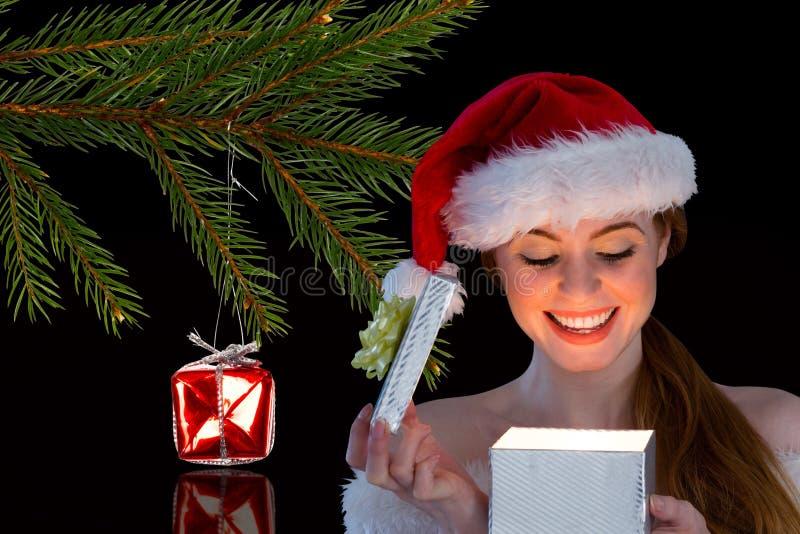 Donna felice in cappello di Santa che apre il suo contenitore di regalo nella notte fotografia stock libera da diritti