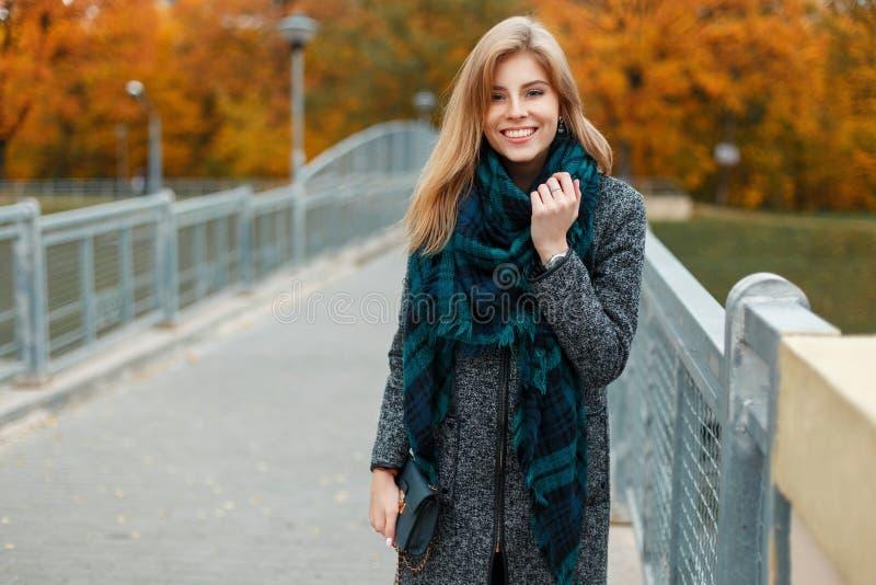 Donna felice in cappotto di autunno con la sciarpa che esamina macchina fotografica immagine stock libera da diritti