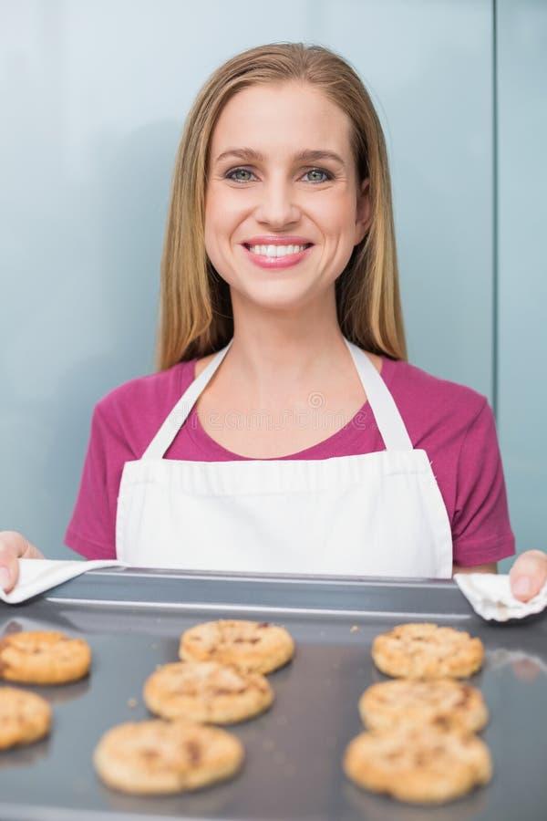 Donna felice casuale che mostra il vassoio di cottura con i biscotti immagine stock