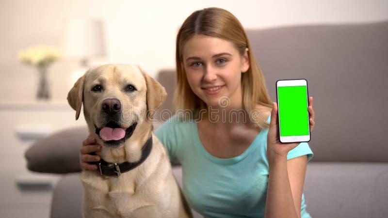 Donna felice che abbraccia un cagnolino da lavoro, che mostra uno smartphone verde, un'app per animali fotografie stock