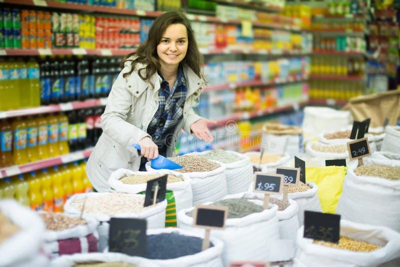 Donna felice che acquista lenticchia in negozio immagini stock