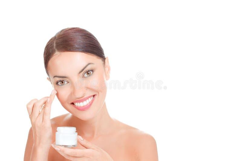 Donna felice che applica crema sul fronte fotografia stock libera da diritti
