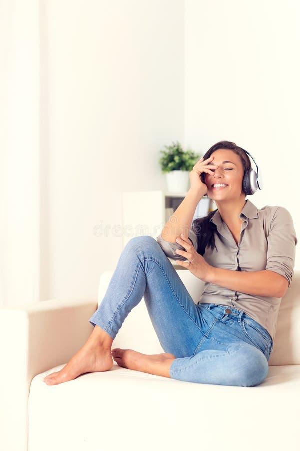Donna felice che ascolta la musica con le cuffie fotografie stock libere da diritti