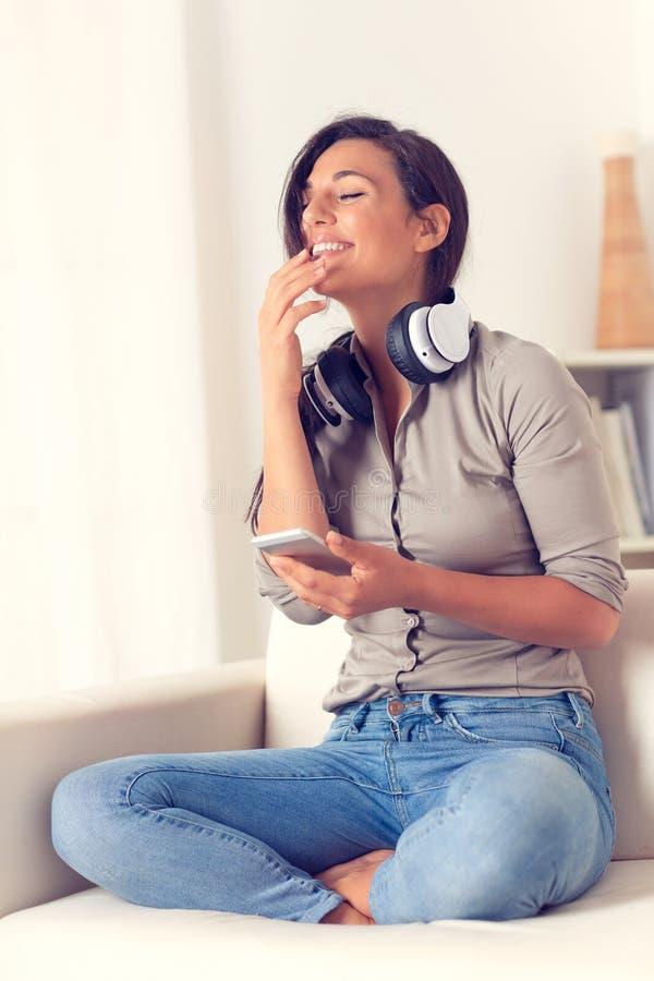 Donna felice che ascolta la musica con le cuffie immagini stock libere da diritti