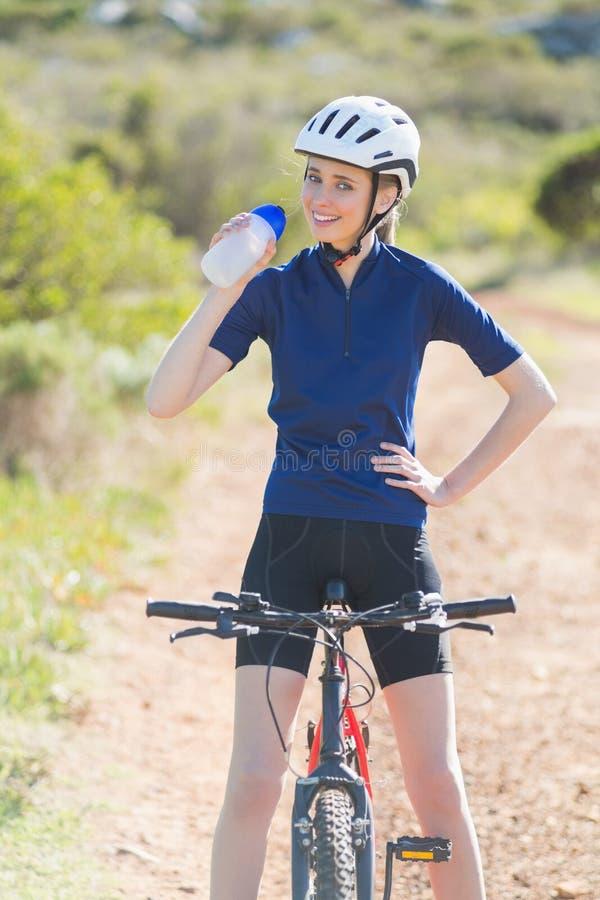 Donna felice che beve dopo il ciclismo fotografia stock libera da diritti